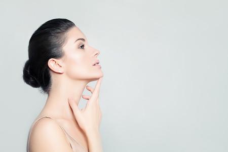 美容: 完美的年輕女子水療模型與健康的皮膚觸摸她的手她的臉。水療美容,面部護理和美容概念