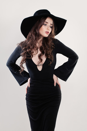 Beautiful Fashion Model Woman in a Black Hat. Young Beauty Stock Photo