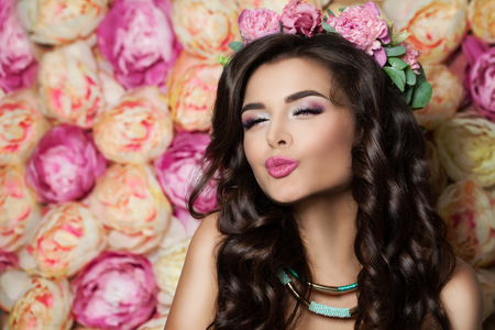 Beautiful Brunette Model Blowing a Kiss on Summer Flowers Background