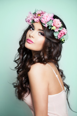 Perfect Model Woman with Summer Pink Flowers. Young Woman with Long Curly