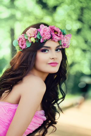 Cute Woman Fashion Model with Long Curly Hair and Flowers Outdoors