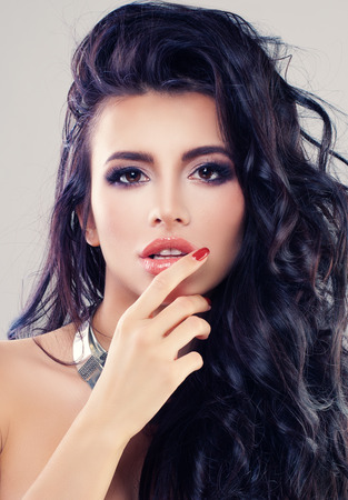 Glamorous Brunette Woman with Curly Hair and Makeup. Fashion Portrait of Beautiful Girl