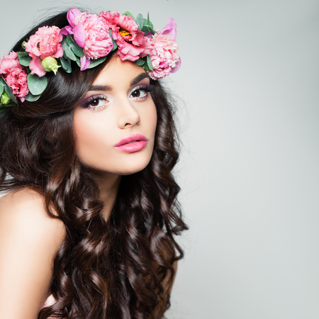 Perfect Brunette Model with Curly Hair and Flowers Wreath. Beautiful Woman with Makeup and Permed Hairstyle on Gray Background 写真素材
