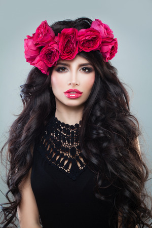 Perfect Woman with Summer Pink Flowers. Long Permed Curly Hair, Roses Wreath and Fashion Makeup