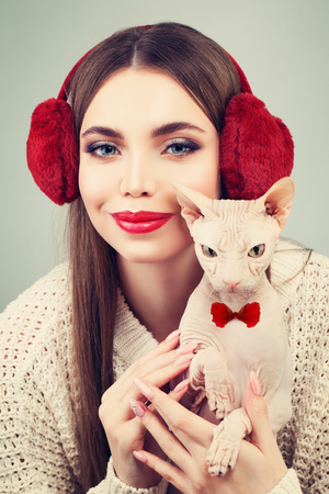 antipode: Beautiful Woman Fashion Model in Furry Ear-muffs White Sweater Holding Hairless Cat. Beauty Winter Girl in Knitted Woolen Cloth Stock Photo