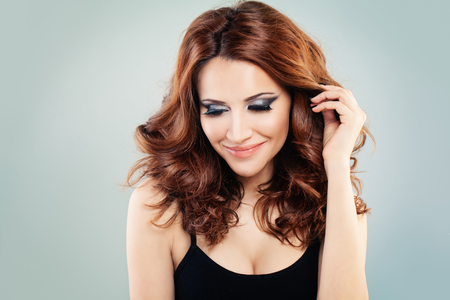 smoky eyes: Pretty Redhead Woman with Makeup and Permed Hairstyle