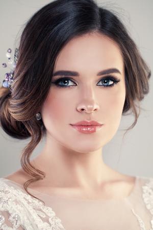 패션 메이크업 및 헤어 스타일, 스튜디오 사진 우아한 웨딩 드레스를 입고 웃는 신부 초상화. 젊은 매력적인 모델