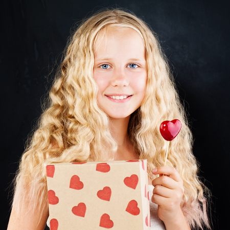 Young Girl Holding Gift Box and Red Heart. Cute Teenager Girl with Long Blonde Hair, Gift and Heart Stock Photo