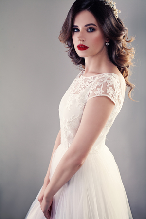 Nice Bride in White Wedding Dress, Pretty Girl Fiancee with Curly Hair and Makeup on Background Stock Photo