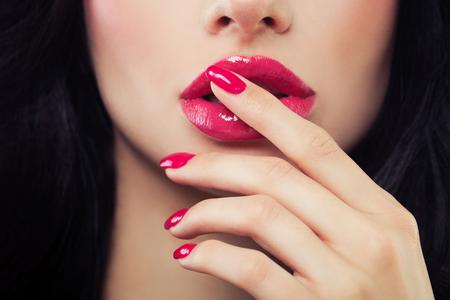 Weibliche Lippen und Nagelnahaufnahme. Rosa Nagellack, Lipgloss und braunes Haar. Beauty-Konzept