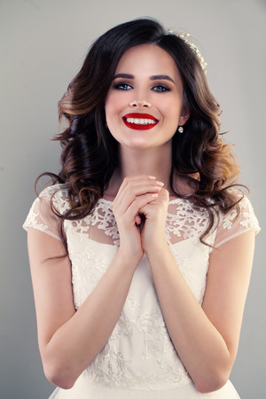 Gorgeous Woman Fashion Model wearing White Dress. Happy Girl with Curly Hair and Make up