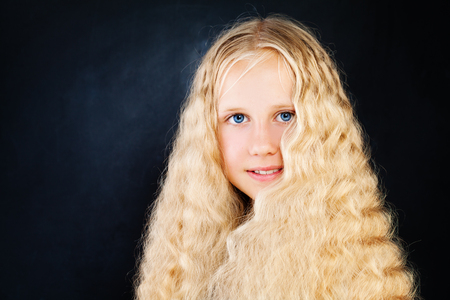 Young Beautiful Girl with Long Blonde Hair. Blonde Child Girl with Curly Hair on Dark Background Stock Photo