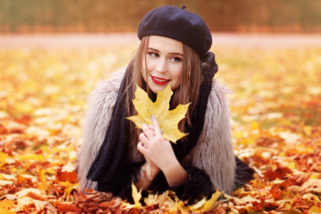 barrett: Autumn Woman Lying on Autumn Leaves in the Park Outdoors