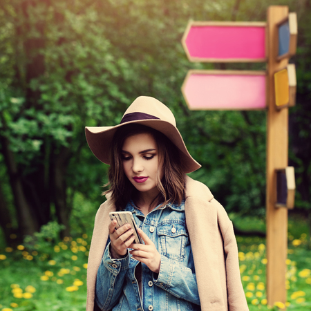Cute Young Woman Looking at her Mobile Phone Outdoors. Journey Stock Photo