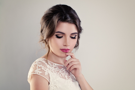 Cute Young Woman Fiancee with Perfect Bridal Hairstyle, Event Makeup and White Dress on Banner Background Stock Photo
