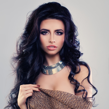 Fashion Portrait of Glamorous Brunette Woman with Long Curly Hair and Makeup
