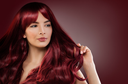 Fashion Model Woman with Red Hairstyle. Redhead Girl on Background with Copyspace Stock Photo