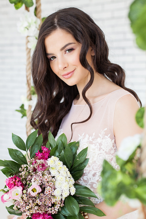 Beautiful Woman with Flowers, Curly Hairstyle and Makeup. Brunette Model Girl