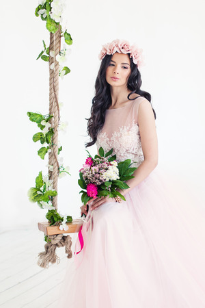 Beautiful Woman Fashion Model wearing Tulle Dress. Cute Girl with Flowers on White Stock Photo