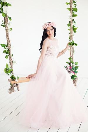 Fashion Model on Swing. Brunette Woman in Pink Dress Stock Photo