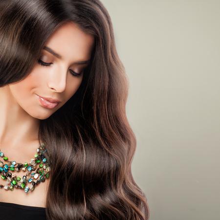 완벽한 아름다움. 긴 곱슬 머리와 메이크업을 가진 젊은 아름다운 여성 패션 모델