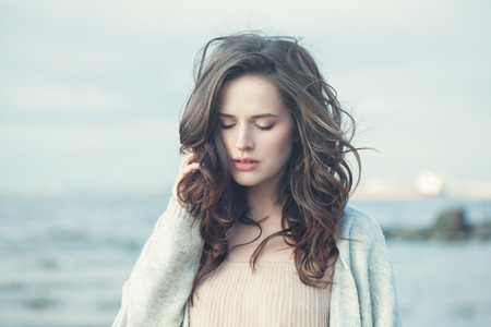 Portrait of a Beautiful Girl with Curly Hair on a Cold Windy Day Outdoors Stock fotó