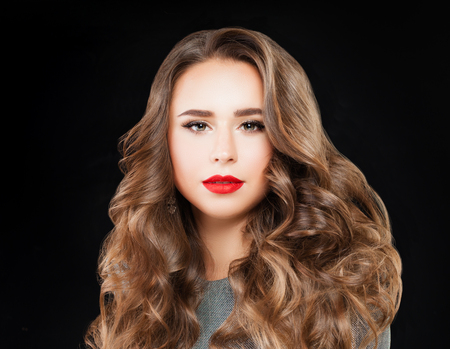 Perfect Woman with Long  Wavy Hair and Event Makeup. Beautiful Model with Red Lips Make up on Black Background