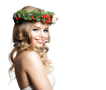 New Year Portrait of Beautiful Smiling Model Woman with Curly Hairstyle, Makeup and Christmas Wreath. Beauty and Cosmetology Concept Stock Photo