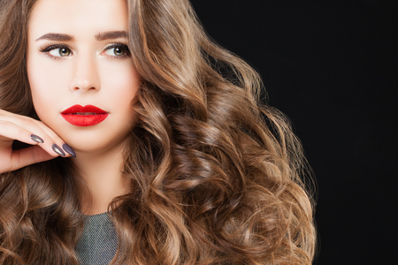 Nice Model Woman with Long Wavy Hair, Perfect Makeup and Manicured Hand. Beautiful Girl with Red Lips Make up on Black Banner Background