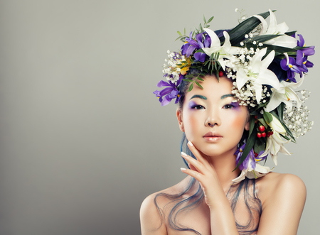 Fashion Portrait of Young Woman with Beautiful Flowers Hairstyle and Fashion Makeup. Fashion Girl with White Lily and Iris Flowers