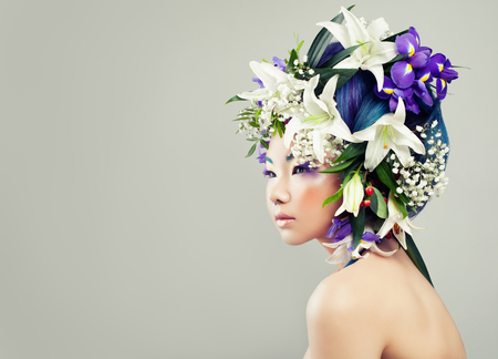Beautiful Asian Model Woman with Colorful Flowers and Fashion Makeup. Spring Fashion Girl with White Lily and Iris Flowers