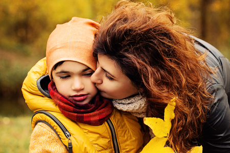 Happy Autumn Family. Loving Mother and Child in Fall Park Outdoors. Parental Care and Love