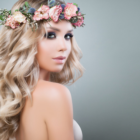 Beautiful Young Woman with Flowers Hairstyle. Blonde Beauty. Fashion Model with Long Permed Curly Hair and Perfect Makeup. Beauty Girl on Background with Copy space