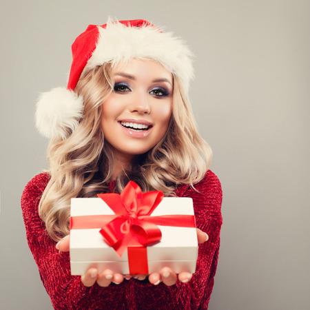 Sonriente modelo de mujer con sombrero de Santa y celebración de regalo de Navidad en el fondo con espacio de copia. Feliz chica de invierno con el pelo rubio, maquillaje y caja de regalo de Navidad. Año nuevo o concepto de Navidad