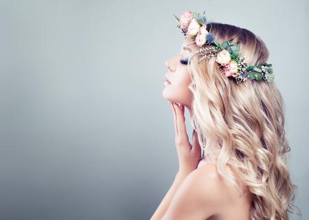 Joven belleza. Muchacha del balneario con las flores rosadas de las rosas, el peinado ondulado largo y la piel sana en fondo azul Foto de archivo - 89403050