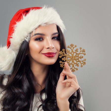 Christmas Woman Fashion Model in Santa Hat with Gold Snowflake. Woman Christmas Concept Stock Photo