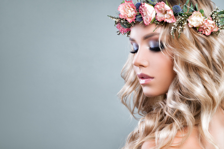 Cute Woman with Pink Roses Flowers and Green Leaves Wreath, Blonde Curly Hair and Healthy Skin. Skincare and Haircare Concept