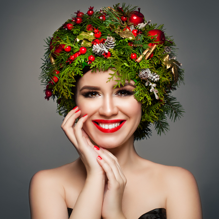 Christmas Woman with Xmas Wreath, Makeup and Manicured Hands. Smiling Model Woman Christmas Concept Stock Photo