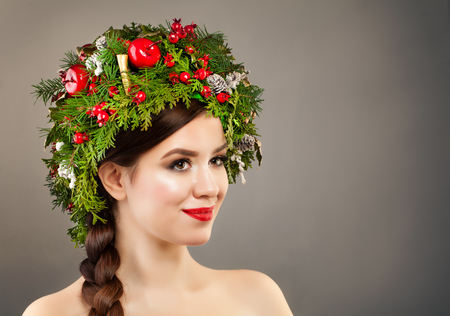 Christmas Woman with Xmas Tree Wreath, Makeup and Braid Hairstyle on Banner Background. Christmas Concept Stock Photo