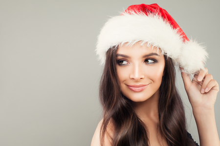 Christmas Woman in Santa Hat on Grey Banner Background with Copy Space. New Year or Christmas Concept