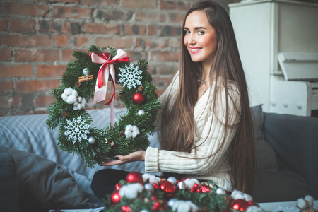 Young Cute Woman Florist with Christmas Tree Wreath with Red Glass balls, Ribbon and White Snowflake