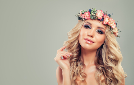 Perfect Young Woman with Flowers Hairstyle. Blonde Beauty. Fashion Model with Long Permed Curly Hair and Makeup. Beauty Girl on Background with Copy space Stock Photo