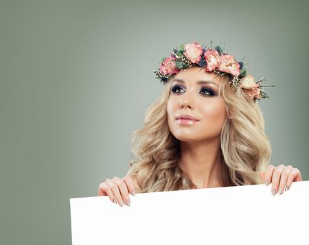 Mannequin belle femme printemps avec des fleurs de roses, coiffure bouclée blonde et une peau saine tenant une bannière de papier vide sur fond vert, Concept de soins de la peau et des cheveux