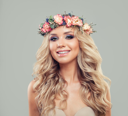 Nice Woman with Summer Pink Flowers. Blonde Beauty. Long Permed Curly Hair and Fashion Makeup
