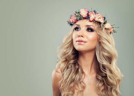 Young Woman with Flowers Hairstyle. Blonde Beauty. Fashion Model with Long Permed Curly Hair and Perfect Makeup. Spring Beauty Girl on Background with Copy space