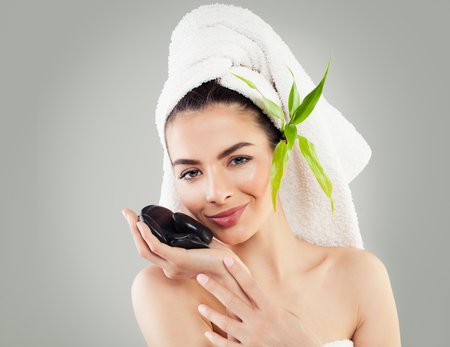 Attractive Spa Female Face. Young Model Holding Hot Black Stones. Spa Woman with Healthy Skin, White Towel and Bamboo Leaves. Massage, Bodycare and Spa Beauty Concept Stock Photo - 95718365