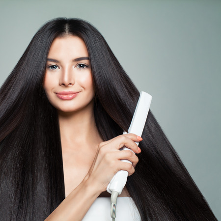 Hairdressing. Woman with Beautiful Long Straight Hair Using Hair Straightener. Cute Smiling Girl Straightening Healthy Brunette Hair with Flat Iron. Hair Ironing, Hairstyle and Haircare Concept Stock Photo