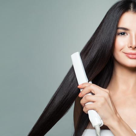 Piękna kobieta z długimi prostymi włosami za pomocą prostownicy do włosów. Ładna dziewczyna uśmiechający się prostowania zdrowe brązowe włosy z prostownicą na szarym tle. Portret Zbliżenie