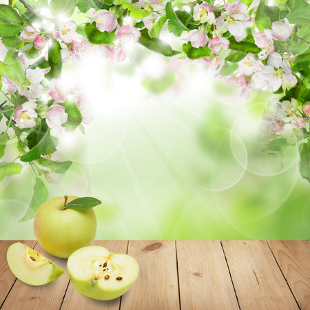 Fruit background with apple fruits, green leaves, flowers and beige empty wooden table with copy space