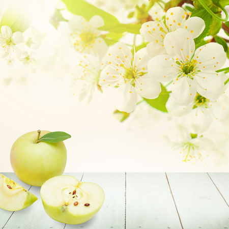 Apple Fruit, Green Leaves, Spring Flowers and White Empty Wooden Board on Abstract Bokeh Light Background